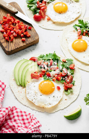 Mexican tortilla with salsa, avocado and egg on concrete background, selective focus. Tasty tacos - Stock Photo