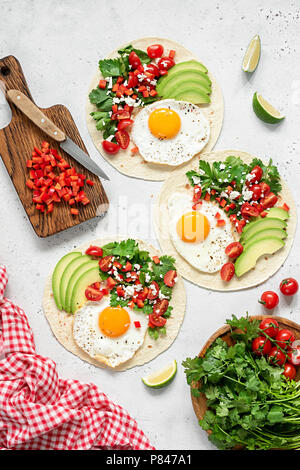 Tortilla with avocado, salsa and egg on concrete background. Top view - Stock Photo