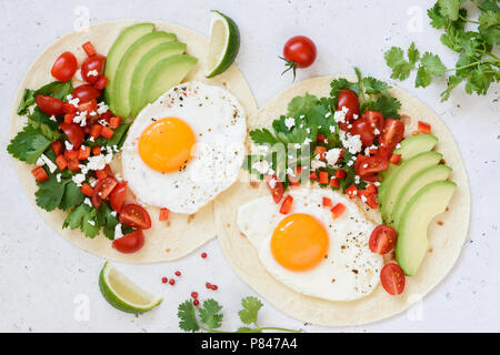 Breakfast tortilla taco with egg, avocado, salsa on bright background, top view - Stock Photo