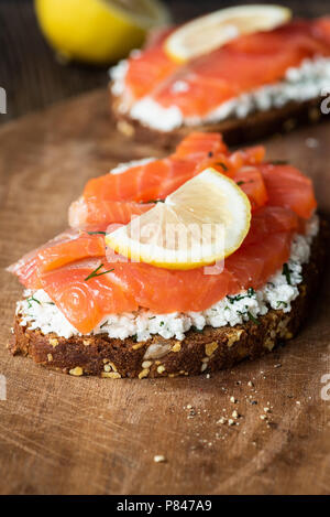 Tasty salmon sandwich with cream cheese and slice of lemon on wooden board, closeup view, selective focus - Stock Photo