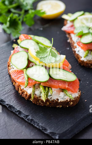 Sandwich with salmon, cream cheese and cucumber on slate background, closeup view, selective focus - Stock Photo