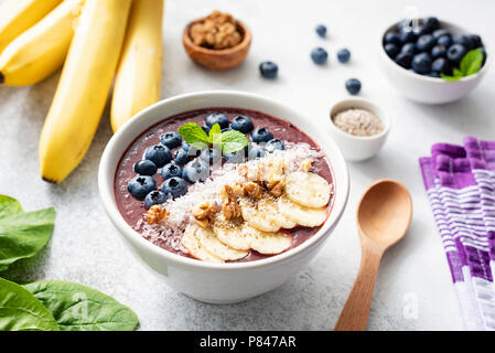 Acai smoothie bowl with superfood toppings on concrete background. Purple smoothie in white bowl with banana, chia seeds, coconut, walnuts and blueber - Stock Photo