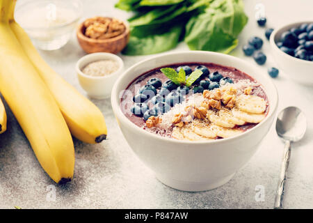 Acai smoothie bowl on grey concrete background. Smoothie with superfood toppings banana, walnut, coconut, chia seeds and fresh blueberries. Selective  - Stock Photo