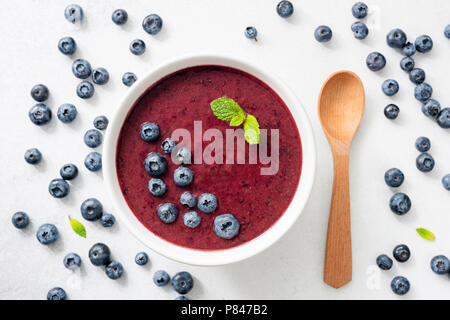 Acai blueberry smoothie bowl on white background top view. Trendy superfood, cleansing, detox and nutrition meal - Stock Photo