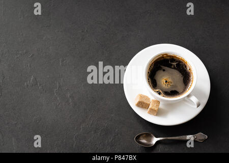 Black coffee cup with brown sugar on black concrete background. Business work desktop with coffee. Coffee break concept with copy space for text, top  - Stock Photo