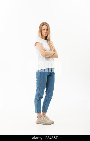 Serious confident young woman with long blond hair dressed in casual wear standing looking at the camera, full body over white - Stock Photo