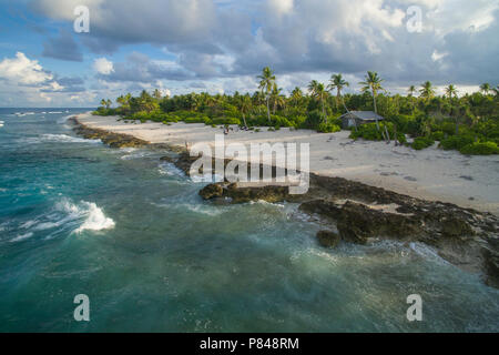 Aerial View of Orona Island, an uninhabited island in the Phoenix Islands, Kiribati. Visitors are standing on the beach. - Stock Photo