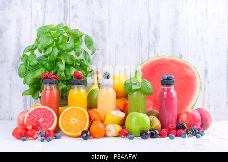 Many different fruits and berries and juices in plastic bottles. Watermelon, banana, applcsin, blueberries, strawberries, basil on a white background. Vitamin and healthy food. Detox. Copy space - Stock Photo