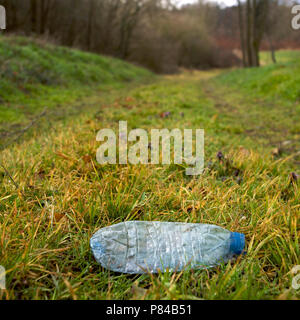 Crushed water bottle on grass abandoned in a grassy path - Stock Photo