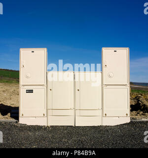 Row of electrical cabinets along an asphalt road in a construction site. France - Stock Photo
