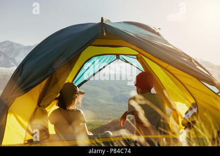 Couple rest in tent against mountains sunset - Stock Photo