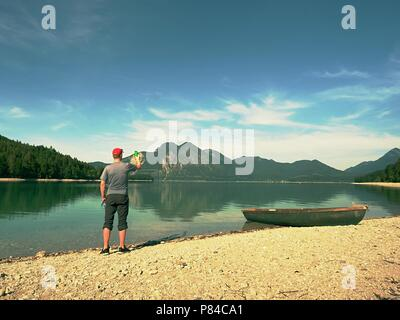 Photo traveler is taking memory photo of lake scenery. Blue lake between high mountains, peaks touch in blue sky. Travel lifestyle concept - Stock Photo