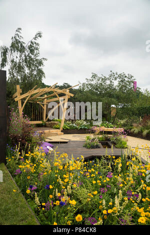 Colourful flowers, timber pergola, bench & pond in beautiful prize-winning show garden, The Great Outdoors - RHS Chatsworth Flower Show, England, UK. - Stock Photo