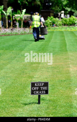 Keep Off The Grass sign in Victoria Embankment Gardens, London, England, UK. Worker cutting the grass - Stock Photo