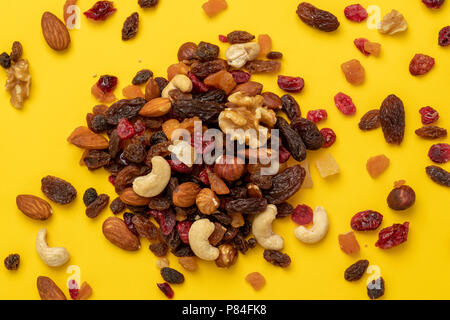 Close up of mix of dried fruits and nuts on a yellow background - Stock Photo