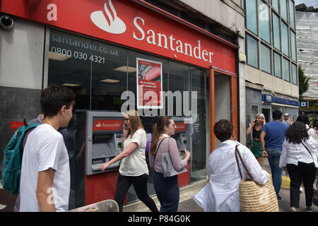 People walk past the Santander bank in Notting Hill, London, next to RBS. As part of a programme of closures this branch will close in October 2018. - Stock Photo