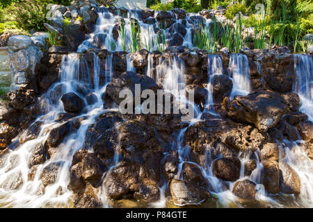 Landscape photography, a beautiful waterfall between the stones flowing light water - Stock Photo