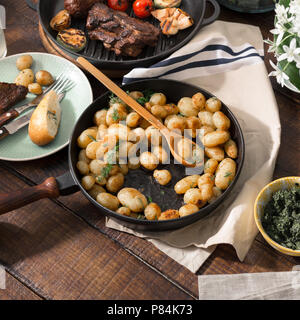Fried young potatoes in a cast-iron frying pan on wooden table with grilled meat. Concept dinner table - Stock Photo