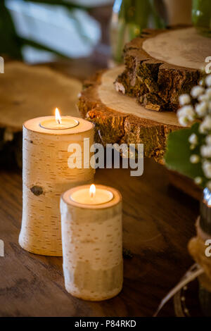 The candles in birch trunk, christmas and wedding decoration, wooden discs are in the background - Stock Photo