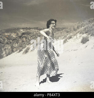 1950s, summertime and a young lady in a long patterned dress playing frisbee on a sandy beach, England, UK.