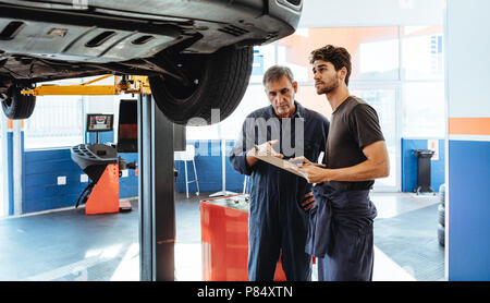 Two car mechanics making a list on clipboard while examining the car. Mechanics making list of repairs on a car in auto service station. - Stock Photo