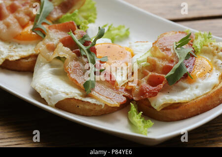Bruschetta with rucola, chrispy bacon and poached egg served on white plate - Stock Photo