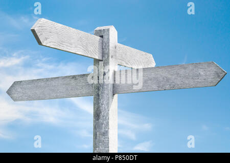 Old weathered wooden signpost against blue sky with four sign choices pointing in different directions. - Stock Photo