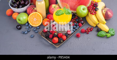Juice in bottles, different and in a glass. Assorted berries and fruits. Gray background. Detox food. Copy space - Stock Photo