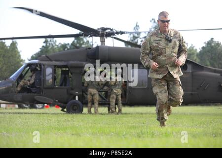 A cadre member departs from the UH-60 Black Hawk helicopter during the Operation Order Event at the 2018 U.S. Army Reserve Best Warrior Competition at Fort Bragg, North Carolina, June 13, 2018, June 13, 2018. U.S. Army Reserve Soldiers compete all day and into the night, pushing themselves at every event during the six-day 2018 U.S. Army Reserve Best Warrior Competition. (U.S. Army Reserve photo by Spc. Devin A. Patterson) (Released). () - Stock Photo