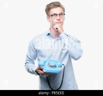 Young handsome blond man holding vintage telephone serious face thinking about question, very confused idea - Stock Photo
