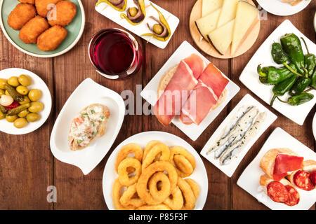 The food of Spain. Overhead closeup photo of various Spanish tapas on a dark rustic texture. Jamon, cheese, wine, calamari rings, gildas, padron peppe - Stock Photo