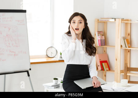Shocked young business woman surprised with something in front sitting in modern office. - Stock Photo