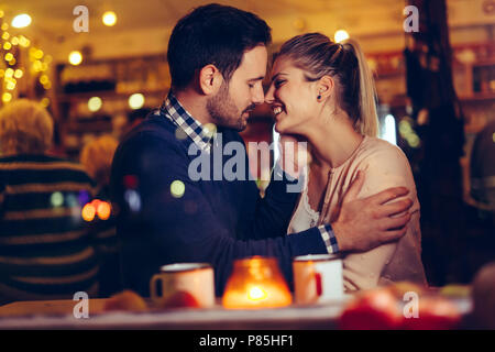 Romantic couple dating in pub at night - Stock Photo