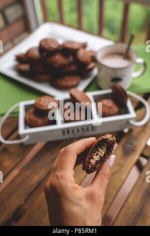 Fudge brownie cookies with penut and cheese filling on white plate on wooden background with cacao on the mug. - Stock Photo