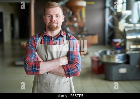 Waist up portrait of modern bearded man wearing apron posing standing confidently with arms crossed against roasting machines in artisan coffee house, - Stock Photo