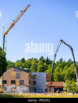Builders working with very large crane pouring concrete at construction site - Stock Photo