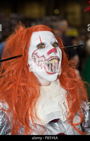 A female cosplayer dressed as Pennywise the clown from the Stephen King novel and movie IT at a comic con event in Birmingham, UK - Stock Photo