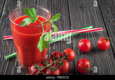 Glass of tomato juice on wooden table - Stock Photo