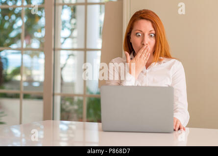 Redhead woman using computer laptop at home cover mouth with hand shocked with shame for mistake, expression of fear, scared in silence, secret concep - Stock Photo