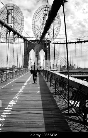 Black and white picture of the Brooklyn bridge with a leaving man - Stock Photo