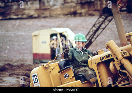 Dragline and Workers at Site of Oil Spill Clean - Up Operations on the San Juan River in Monument Valley, Utah, 10 1972 - Stock Photo