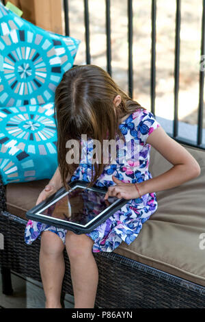 Dark haired, pretty pre-teen caucasian girl, playing with tablet. Charlie Organ Model Relesae #104. Cranbrook, BC, Canada - Stock Photo