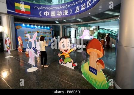 Nay Pyi Taw, Myanmar. 9th July, 2018. A visitor takes photos with her mobile phone during a ceremony of launching Chinese cartoon series program in Nay Pyi Taw, Myanmar, July 9, 2018. Credit: U Aung/Xinhua/Alamy Live News - Stock Photo