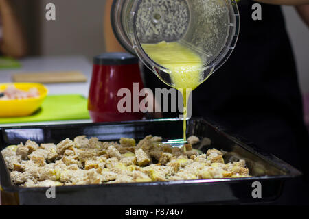 Garlic sauce pours on crackers for a Caesar salad - Stock Photo