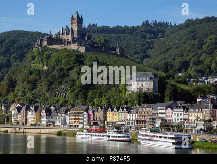 The Castle (Reichsburg), with its vineyard, towers over colourful half-timbered buildings along the bank of the River Moselle in Cochem, Germany.