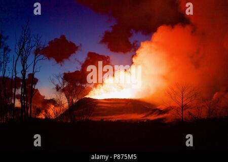 Lava and ash pour out from the summit of the Kilauea volcano crater following the collapse July 6, 2018 in Hawaii. The recent eruption continues destroying homes, forcing evacuations and spewing lava and poison gas on the Big Island of Hawaii. - Stock Photo