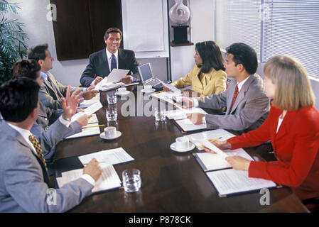 1997 HISTORICAL GROUP OF MULTI ETHNIC BUSINESS PEOPLE MEETING IN OFFICE CONFERENCE ROOM - Stock Photo