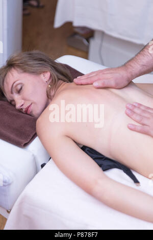 Spa woman. Female enjoying relaxing back massage in cosmetology spa centre. Body care, skin care, wellness, wellbeing, beauty treatment concept. - Stock Photo