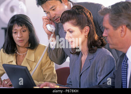 1997 HISTORICAL CAUCASIAN BUSINESS WOMAN SITTING WITH LAPTOP AT MULTI ETHNIC GROUP MEETING - Stock Photo