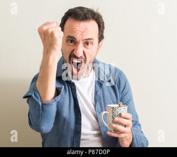 Senior man drinking coffee in a mug annoyed and frustrated shouting with anger, crazy and yelling with raised hand, anger concept - Stock Photo
